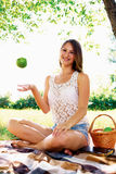 Girl throws up an apple. beautiful girl has a rest in the Stock Photo