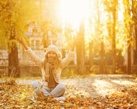 Girl throws up fallen leaves. Autumn. Royalty Free Stock Photography