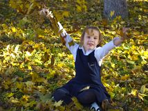 Girl throws up yellow leaves stock image