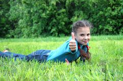 Girl with thumb on a green grass royalty free stock images