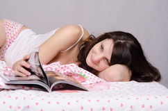 Girl thumbs through a magazine while lying in bed Stock Photography