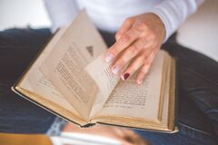 Girl thumbs through the old book Royalty Free Stock Photography