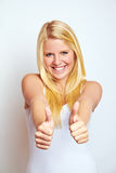 Girl with thumbs up. Half body portrait of smiling blond haired girl with two thumbs up, white studio background Stock Photos