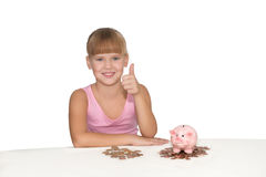 Girl with thumbs up gesture and piggy bank on the table  isolate Royalty Free Stock Image