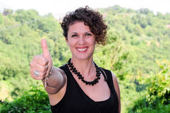 Girl with thumbs up on landscape Stock Photo