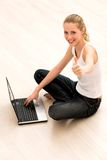 Girl with thumbs up using laptop Stock Photo