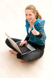 Girl with thumbs up using laptop Royalty Free Stock Images