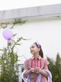 Girl In Tiara And Feather Boa Holding Balloon Stock Photo