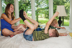 Girl tickling feet of laughing boys Royalty Free Stock Photos