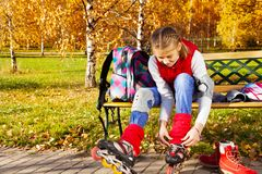 Girl tie shoelaces on rollerblades Stock Photography