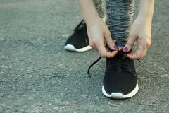 Girl ties up her shoelaces Royalty Free Stock Image