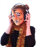 Girl a tiger in headsets listens music. Stock Image