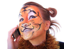 Girl a tiger speaks on a mobile telephone. Royalty Free Stock Photo