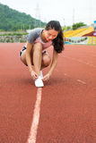 Girl tightening shoelaces on a jogging track Royalty Free Stock Images