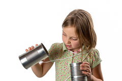 Girl with Tin Can / String Phone - Expressing Skepticism. Girl tangled up in string from a tin can phone. Skeptical of this old-school technology. Close-up stock images