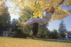 A girl on a tire swing in autumn Royalty Free Stock Photos