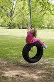 Girl on tire swing Stock Photo