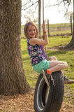 Girl on tire swing. Smiling young preteen girl on a tire swing Royalty Free Stock Photo