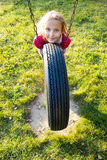 Girl on Tire Swing. Young girl in autumn park having fun on tire swing royalty free stock image