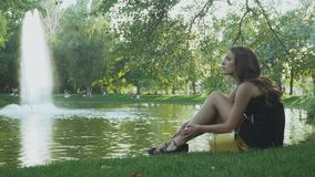 Girl tired from high heels and relax on green grass near the pond stock footage