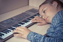 Girl is tired of learning to play the synthesizer and sad lies on the table. Royalty Free Stock Images