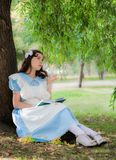 Girl tired of reading boring book sitting under a tree. Girl in the image of a character from a fairy tale tired of reading boring book sitting under a tree Stock Image