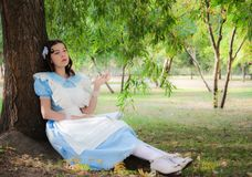 Girl tired of reading boring book sitting under a tree. Girl in the image of a character from a fairy tale tired of reading boring book sitting under a tree Royalty Free Stock Image