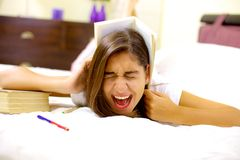 Girl tired of studying screaming with book on head royalty free stock photos