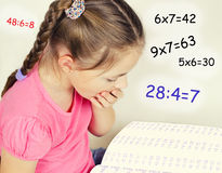 The girl tired to solve the examples in mathematics. A girl about ten years yawns, looking into a large notebook with math problems. It gives examples of the Royalty Free Stock Photo