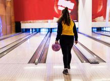 Girl about to roll a bowling ball hobby and leisure concept Stock Photos