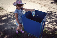 Girl to throw away trash in the trash. Well brought-up child, throwing a plastic bottle in the trash Stock Photo