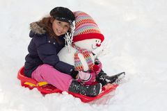 Girl with toboggan and snowman Royalty Free Stock Image
