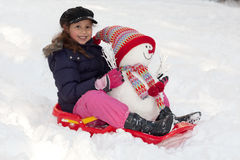 Girl with toboggan and snowman Royalty Free Stock Photography