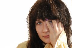 Girl toching her face. Young attractive brown haired girl in yellow shirt touching her face Royalty Free Stock Photos