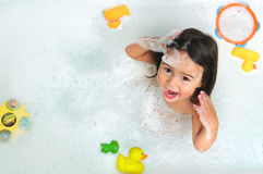 Girl Toddler in bath tub. A young girl toddler plays with bubbles in the bath tub stock photos