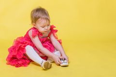 Girl toddler in a pink dress on a yellow background wearing the shoes on his feet.  stock photos