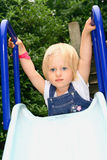 Girl toddler on top of slide. Beautiful girl toddler with blue eyes attempt at going down the slide Royalty Free Stock Photos