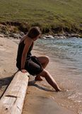 Girl with toes in the sea. Girl on the beach, sitting on a log,  with her toes in the sea Royalty Free Stock Images