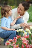 Girl together with mother sits at bed with tulips Royalty Free Stock Images