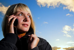 Girl tolking on the phone. Blonde girl tolking on the cell phone over blue cloudy sky Stock Photos