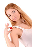 Girl and tomato. Young girl holding a tomato near shoulder royalty free stock photography