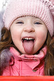 Girl with tongue. Little girl is showing a tongue Stock Image