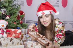The girl took out a large box of little boxes with a gift, lies near the Christmas tree Royalty Free Stock Photos