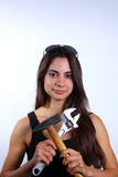 Girl with tools. Beautiful young woman with long brown hair wearing black shirt and sunglasses and holding tools Royalty Free Stock Image