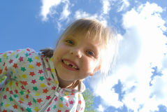 Girl without a tooth. Against the blue sky Stock Photo