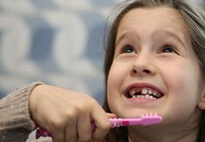 Girl without a tooth while brushing teeth. Young girl without a tooth while brushing teeth in the bathroom Stock Image