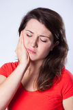 Girl with tooth pain. On gray background stock photo