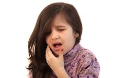 Girl with toothache. Cute little girl with her hand held to her face with painful expression showing toothache Stock Image