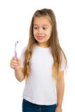 Girl and a Toothbrush. Cute gap toothed girl looking at her toothbrush, Isolated stock image