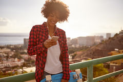 Girl with toothy smile looking at cellphone. Young girl with her skateboard looking at cell phone wearing denim shorts, a white tank top and red and black shirt Royalty Free Stock Image